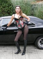 Sexy babe with big tits posing with a muscle car